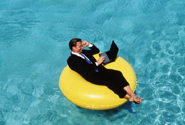 Businessman using laptop on float - Aruba